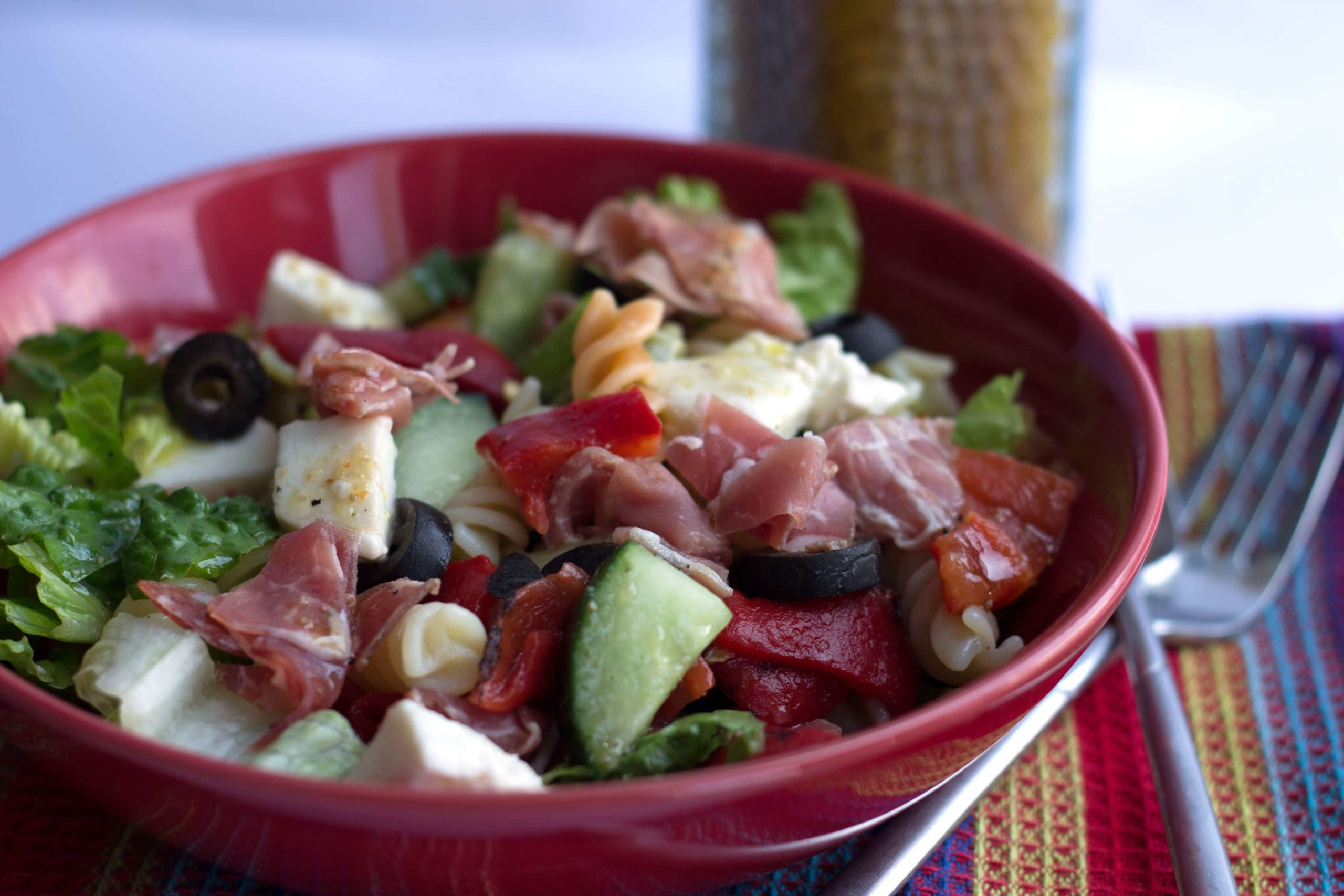 Antipasto Pasta Salad in a maroon colored bowl with forks next to it