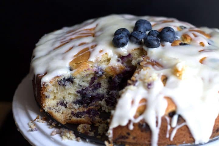blueberry cake with a slice cut out of it showing the blueberries inside the cake