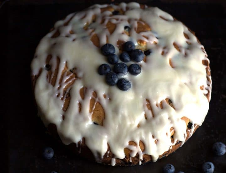 blueberry cake with icing and fresh blueberries on top