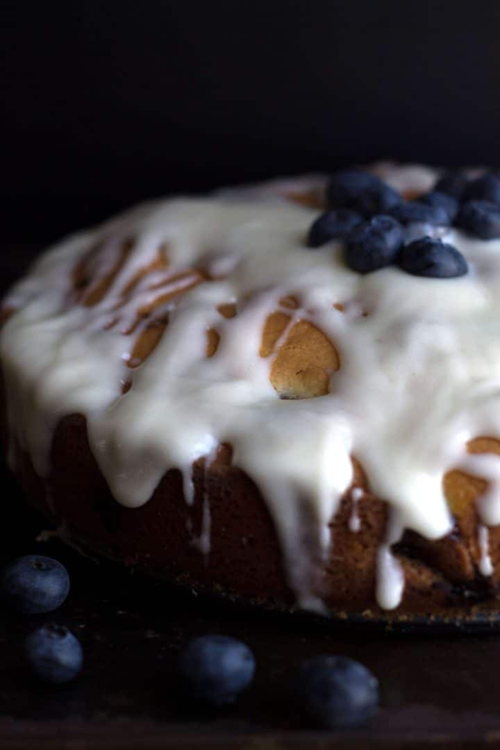 Blueberry cake drizzeled with cream cheese icing and topped with some fresh blueberries