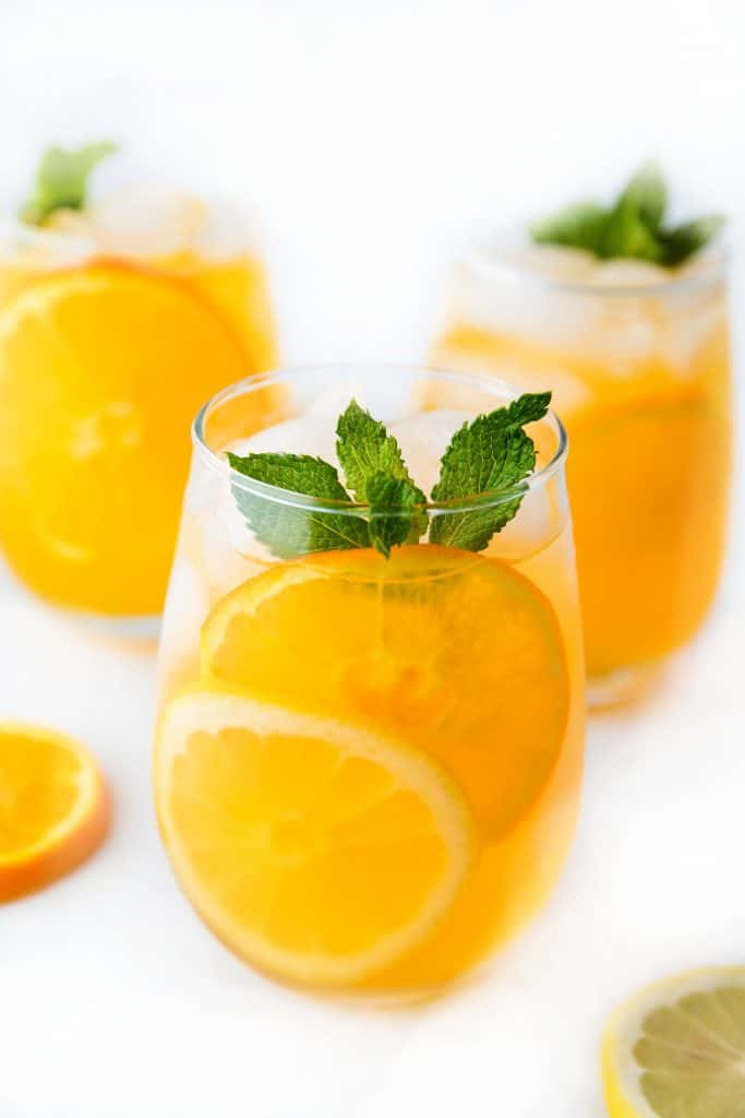 three glasses of citrus punch with a sprig of mint
