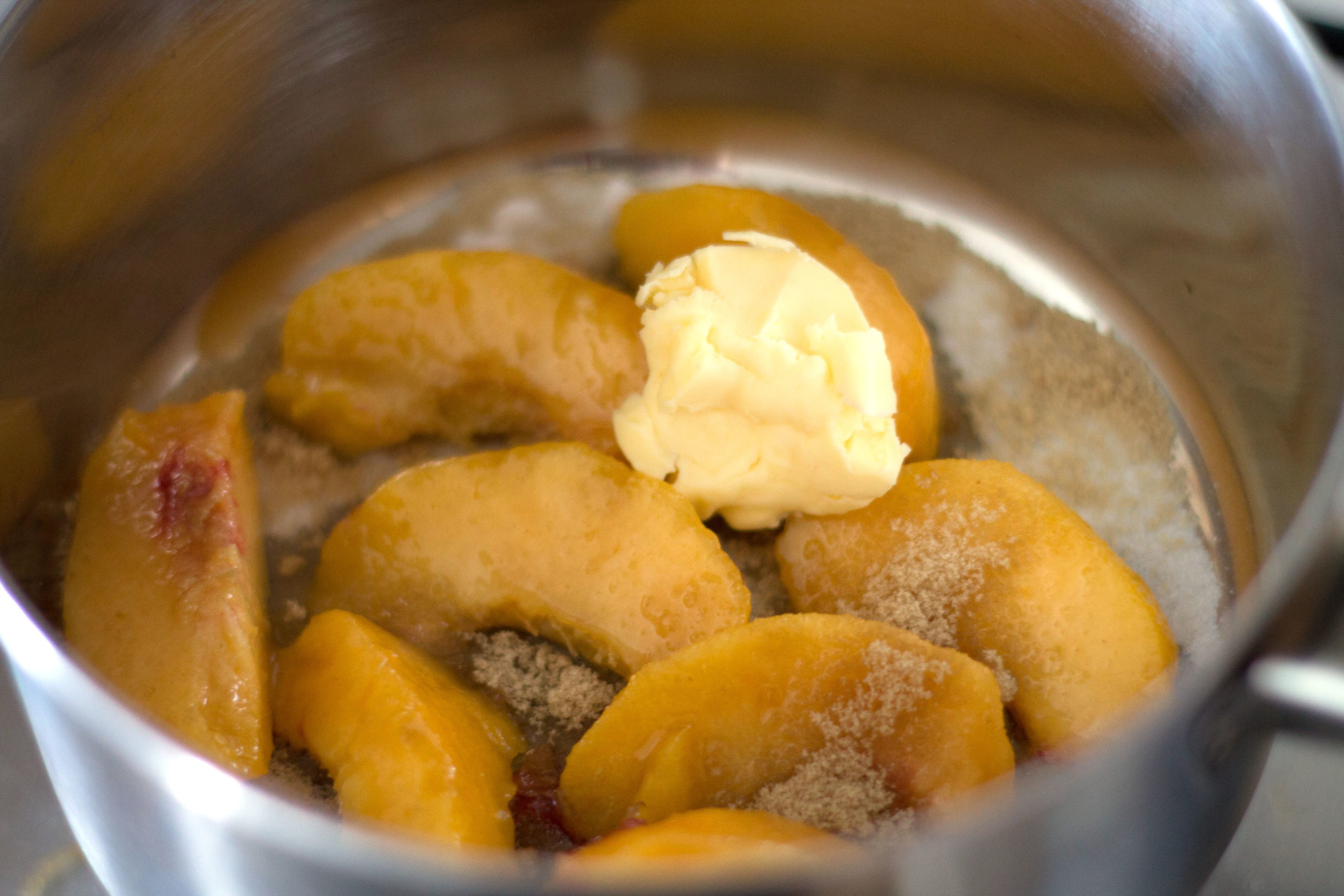 sliced peaches in a pan with brown sugar and butter