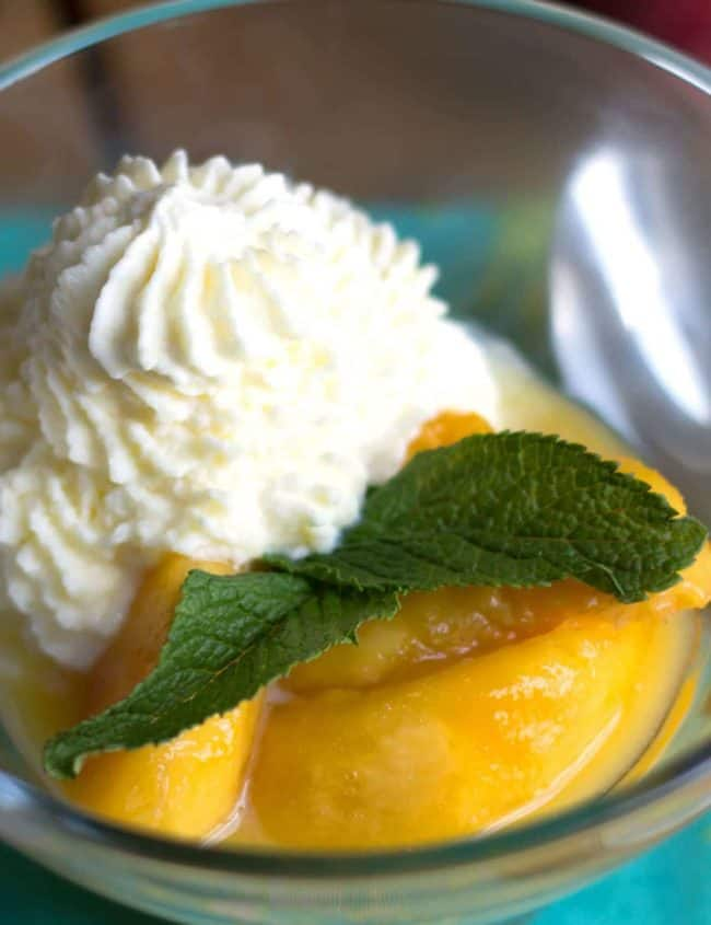 peaches and cream in a glass bowl garnished with mint