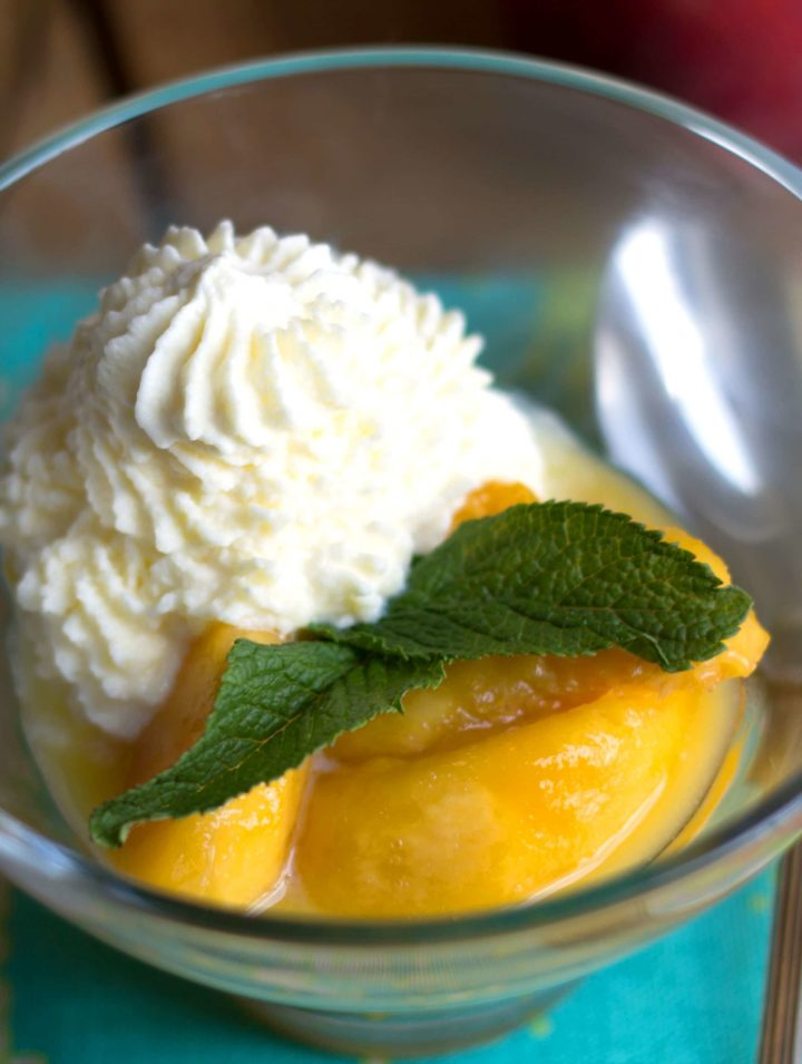 peaches and cream in a clear glass bowl with whipped cream and a mint leaf garnish