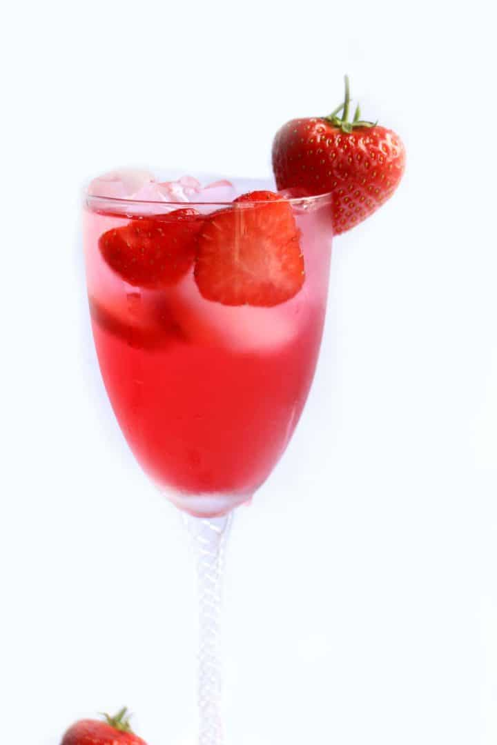 Strawberry Cocktail on a stemmed glass with fresh strawberries in the glass and on the rim of the glass