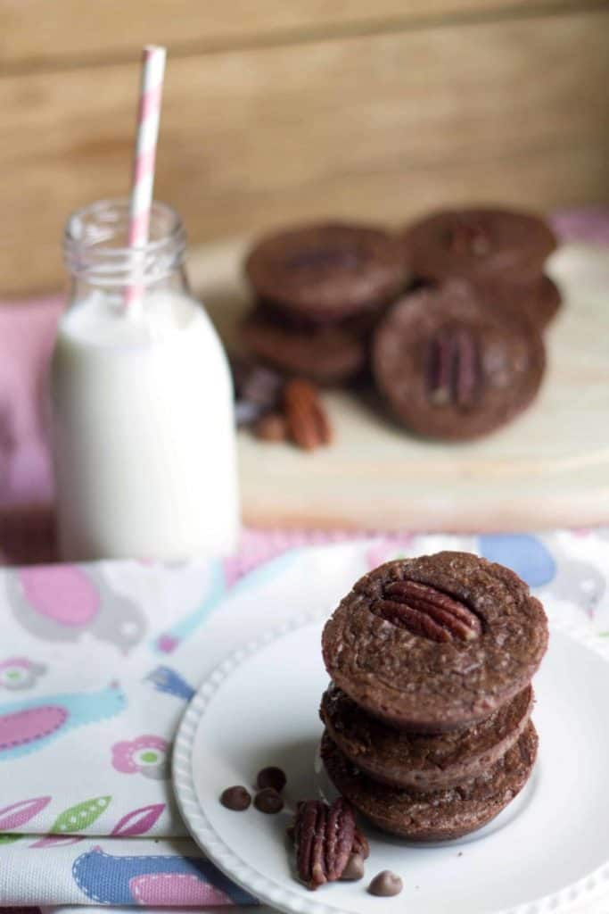 triple chocolate brownie bites on a plate with a milk bottle in the background