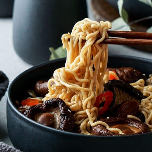 Chinese Mushroom Noodle Soup in a bowl with noodles on chopsticks.