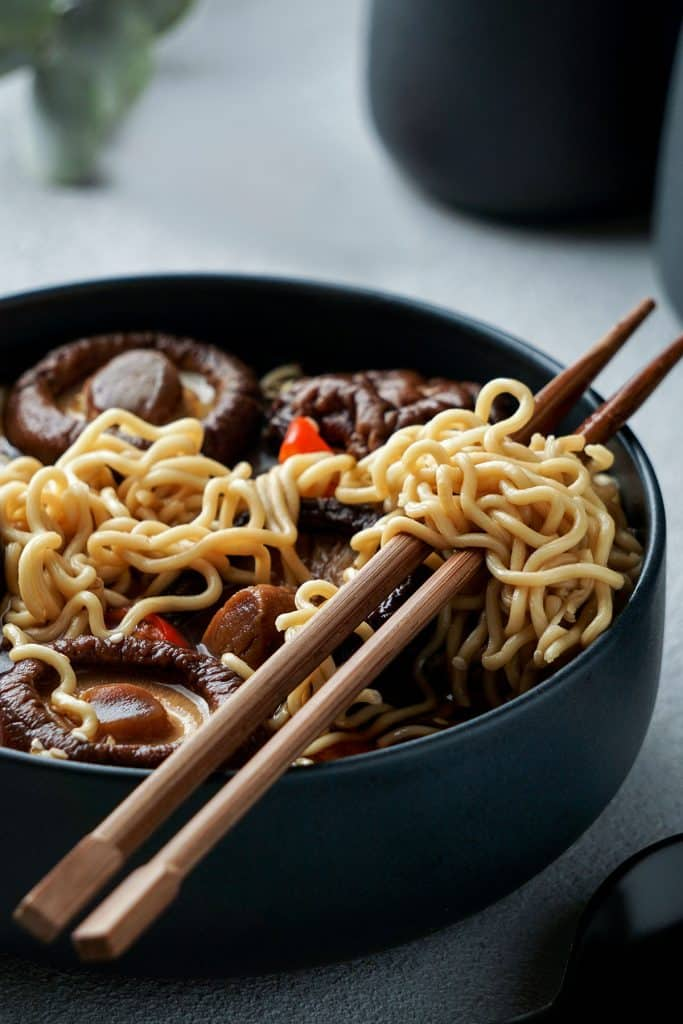 A bowl of chinese noodles with mushrooms and chopsticks ready to serve.