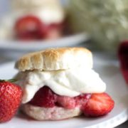 A close up of strawberry shortcake on a plate with fresh strawberries
