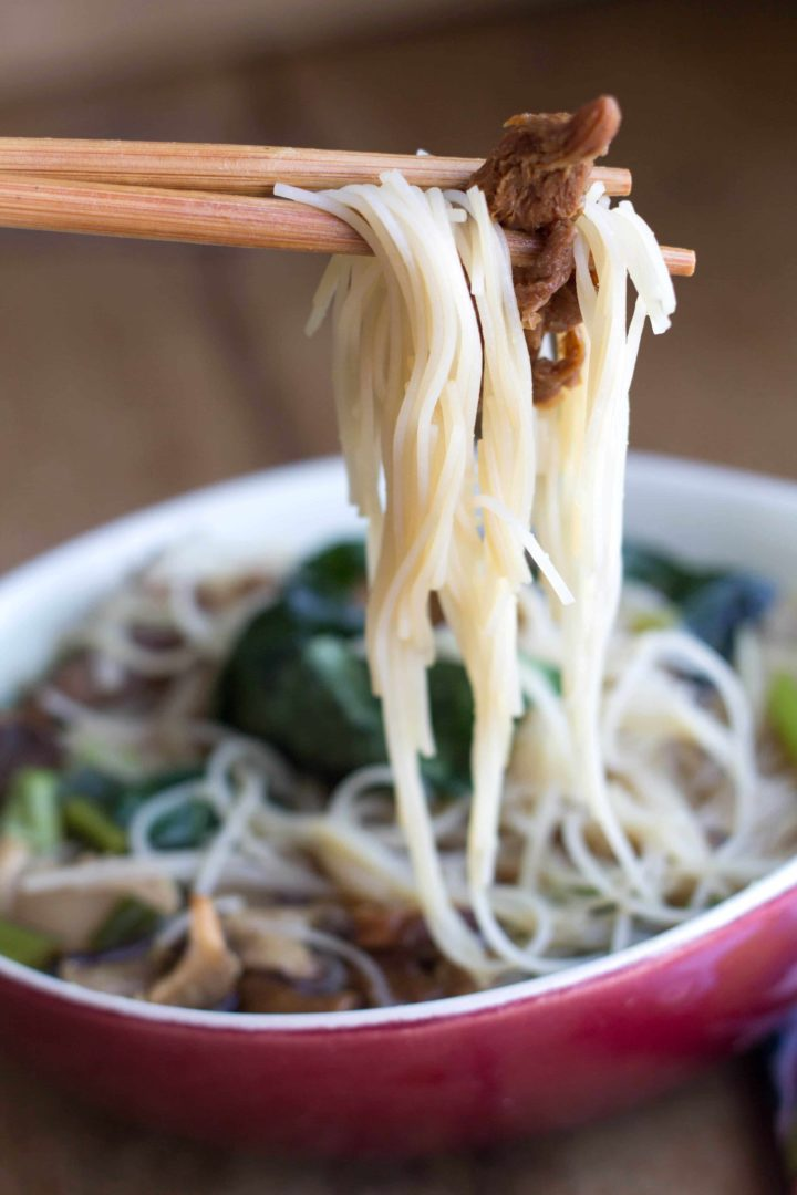 close up of chopsticks with noodles and a mushroom, with a bowl of Chinese mushroom noodle soup in the background