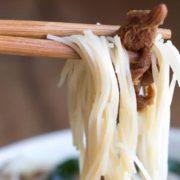 A close up noodles on chopsticks