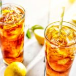 Two tall Glasses of Sweet Lemon Iced Tea with lots of ice and lemon sclices