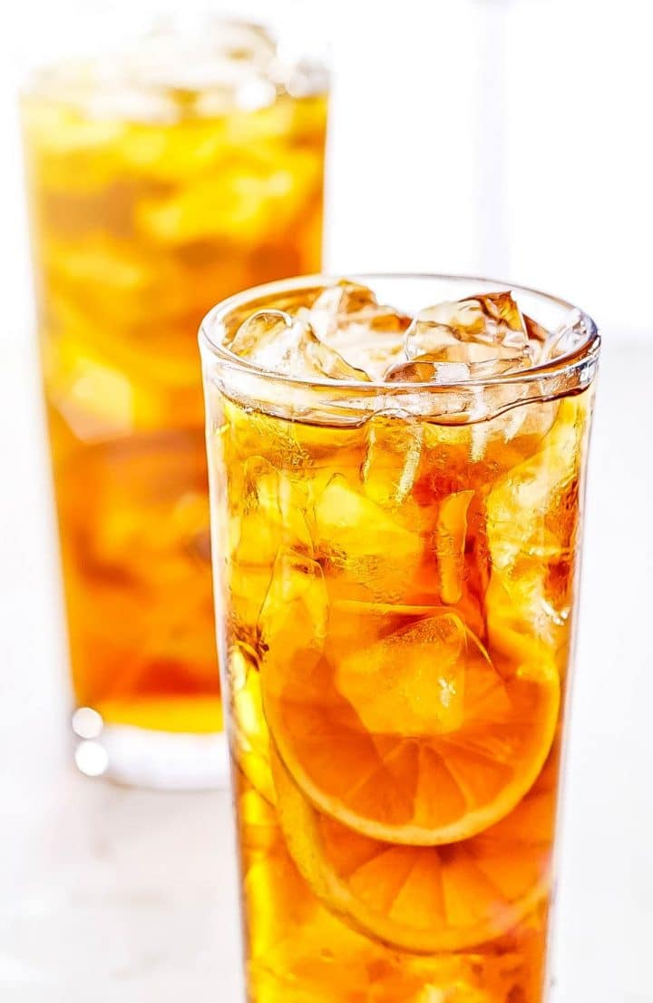 Two tall Glasses of Sweet Lemon Iced Tea with lots of ice and lemon slices