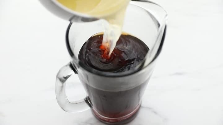 Lemon juice pouring into a pitcher of tea
