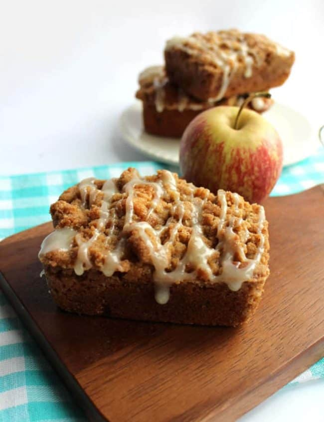 Apple Crumb Cakes on a board with more cakes and an apple behind it