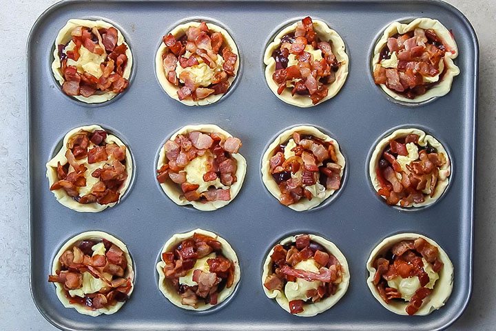The cooked bacon scattered over the top of the filled tarts