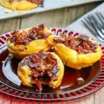 Three Cranberry Brie Tarts with Bacon & Red Onion on a red plate with more tarts in the background