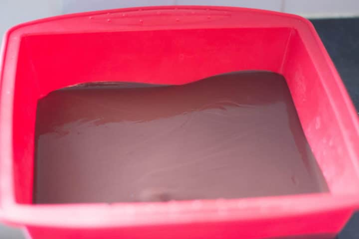 a red silicone pan with the melted chocolate spread in the bottom
