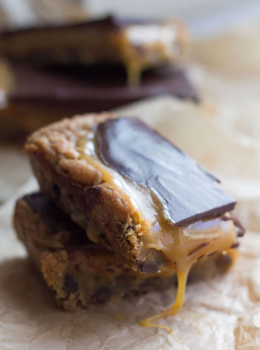 Two slices of the blondies stacked with salted caramel oozing from the side of the top one
