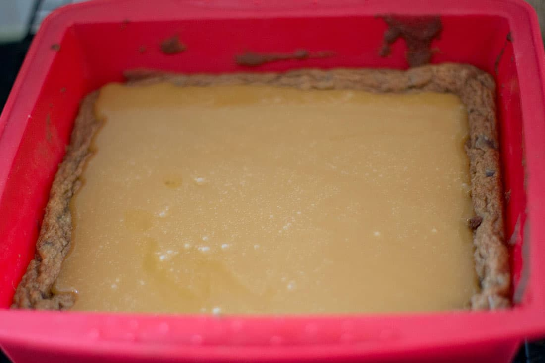 The set caramel sitting on top of the blondie base still in the pan
