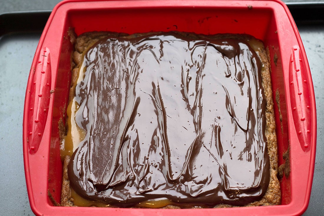 The melted dark chocolate spread over the caramel and blondie base still in the pan
