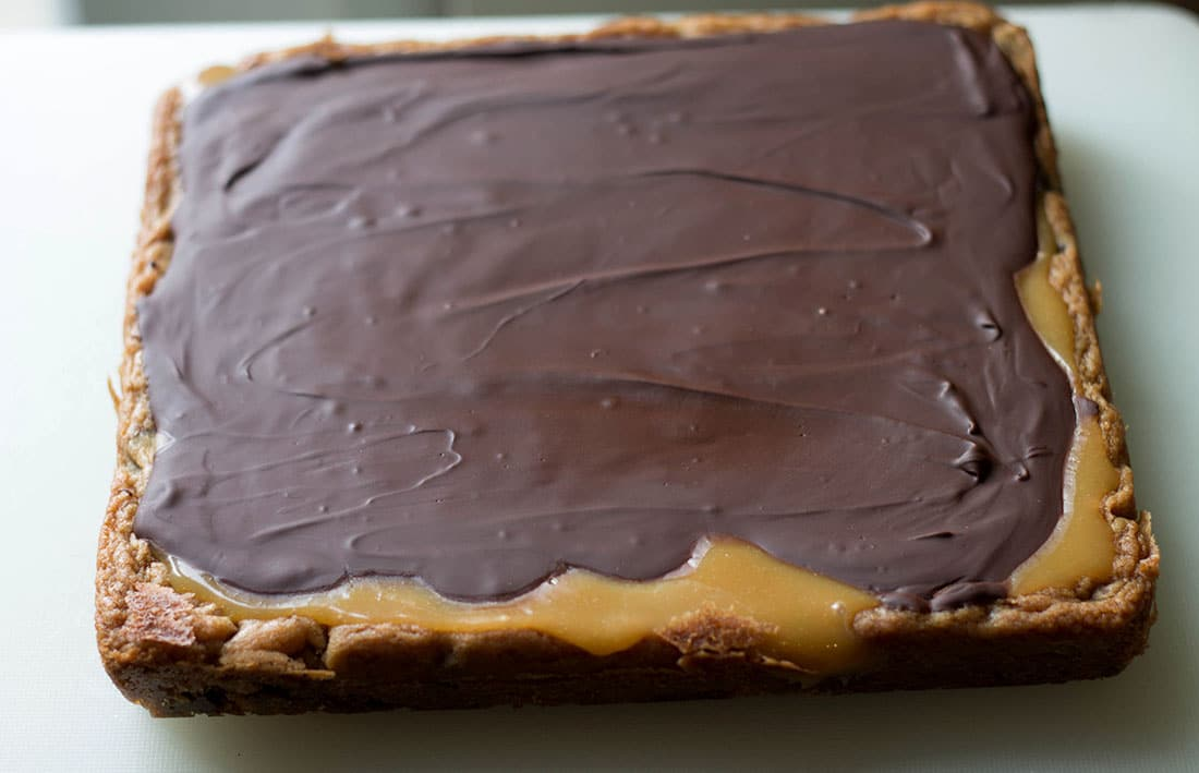 chocolate and caramel covered blondies before cutting