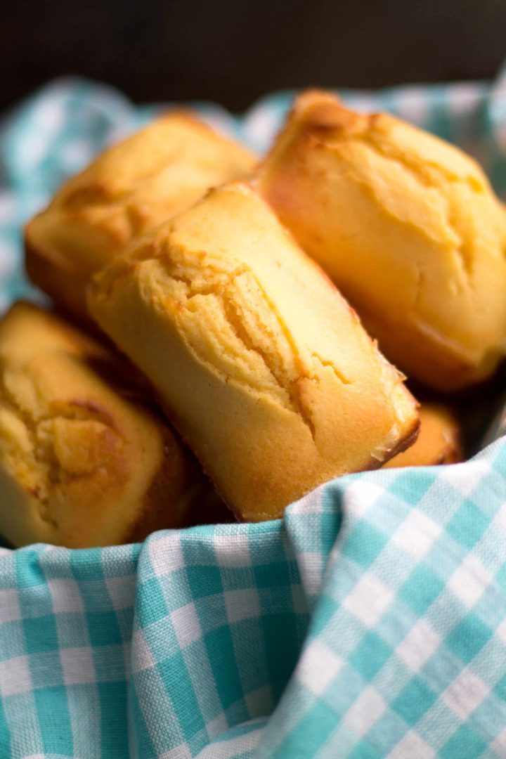 Mini Honey Cornbread loaves piled high in a bread basket lined with a cloth