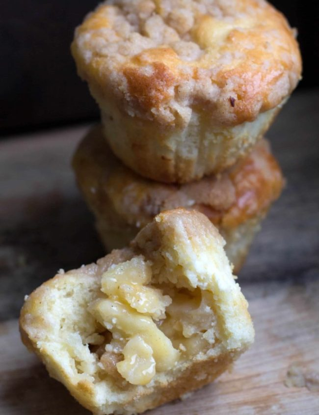 Apple cheesecake muffins with one muffin cut in half to show the centre