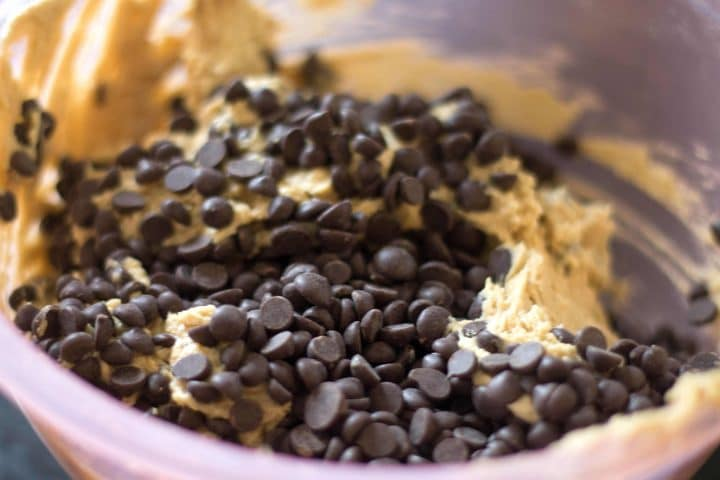 A bowl with the cookie dough topped with dark chocolate chips.