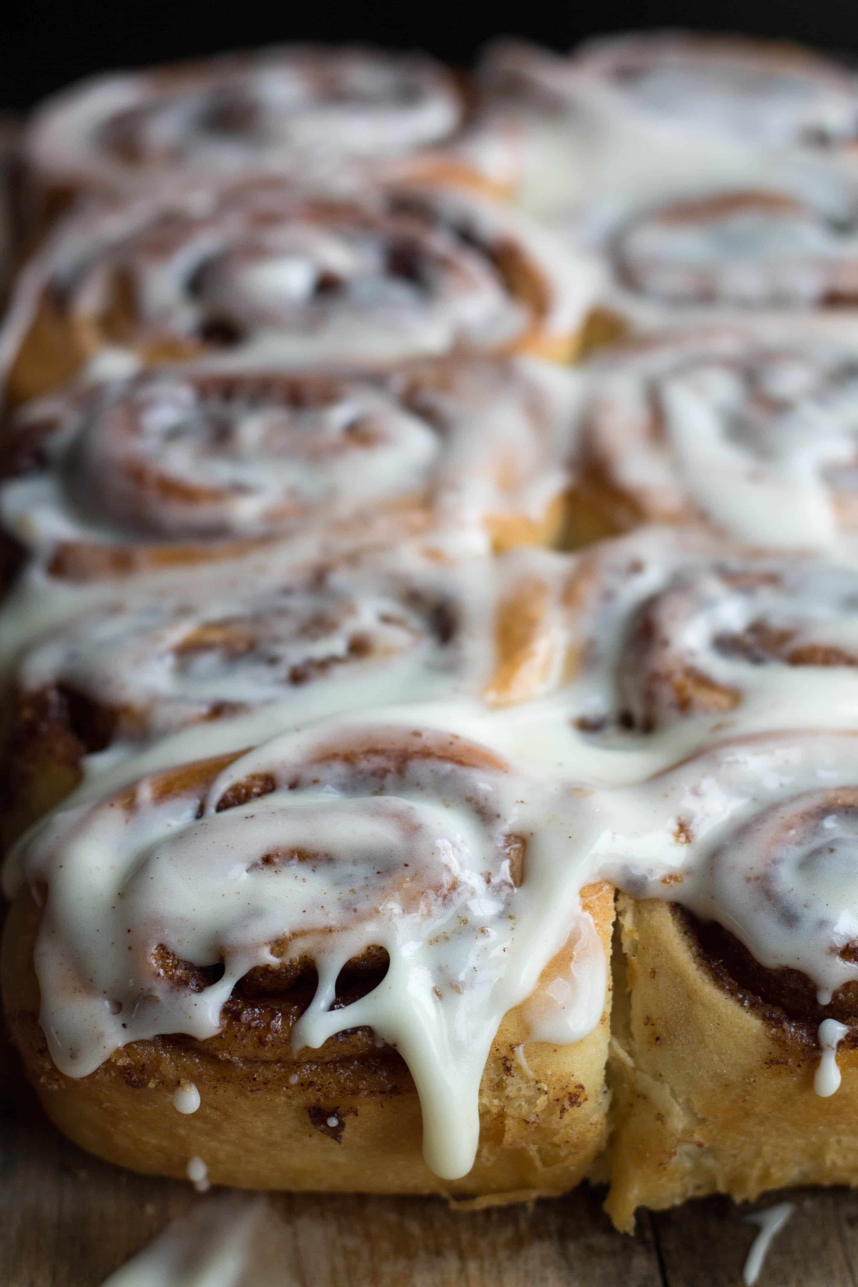 A close up of cinnamon buns with icing