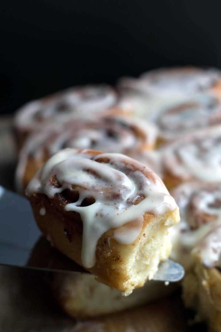 Quick Rise Cinnamon Roll on a serving slice with the rest of the batch in the background