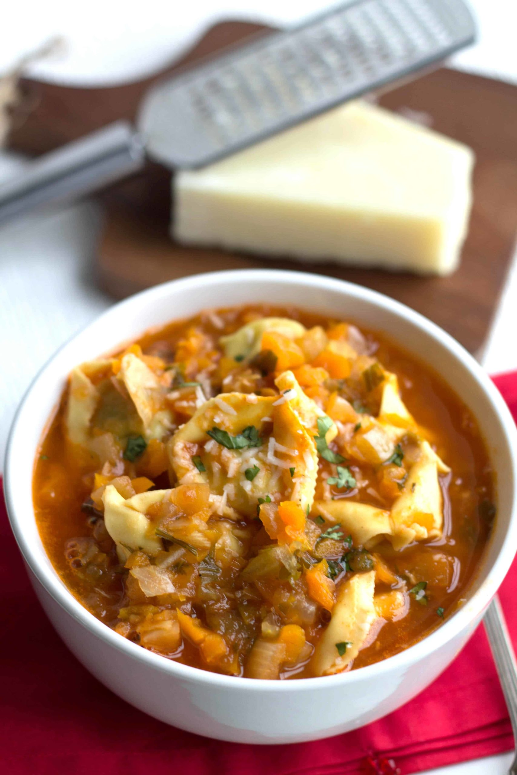 tortellini vegetable soup in a bowl with grated parmesan