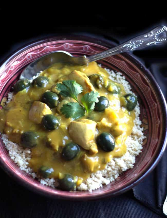 Moroccan Chicken on top of couscous with a spoon in the bowl