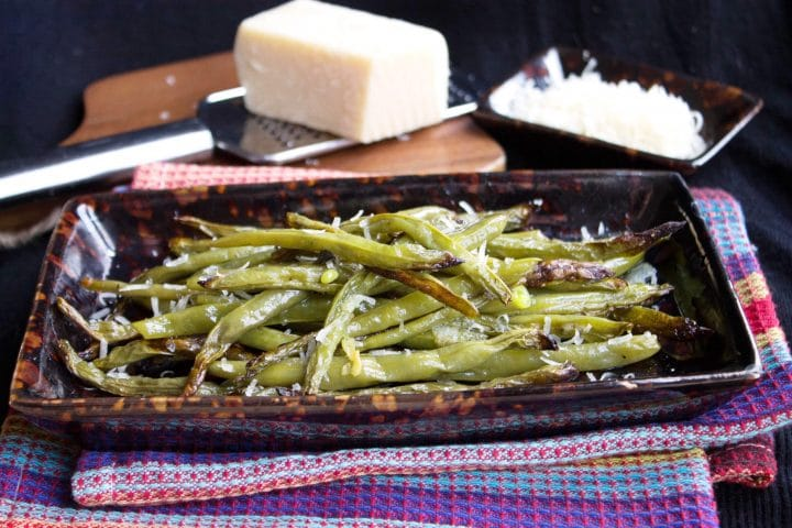 A close up of a plate of Garlic Roasted Green Beans sprinkled with fresh grated Parmesan cheese
