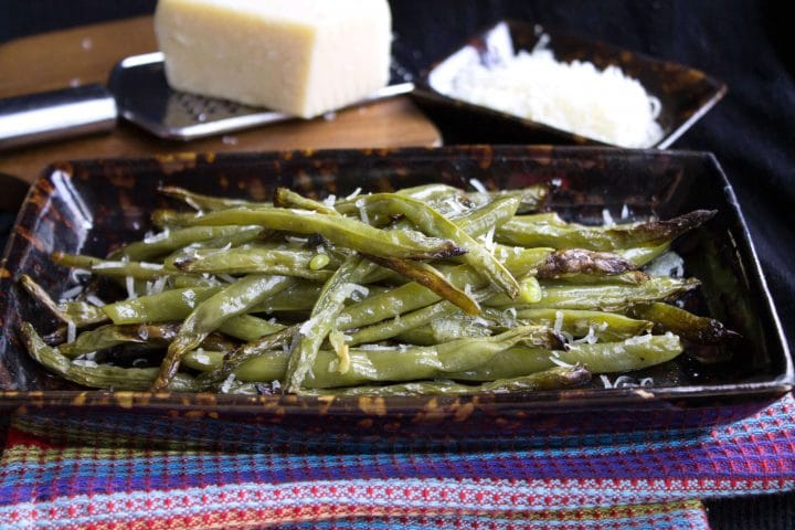 A plate of Garlic Roasted Green Beans with a block of Parmesan cheese and grater in the background