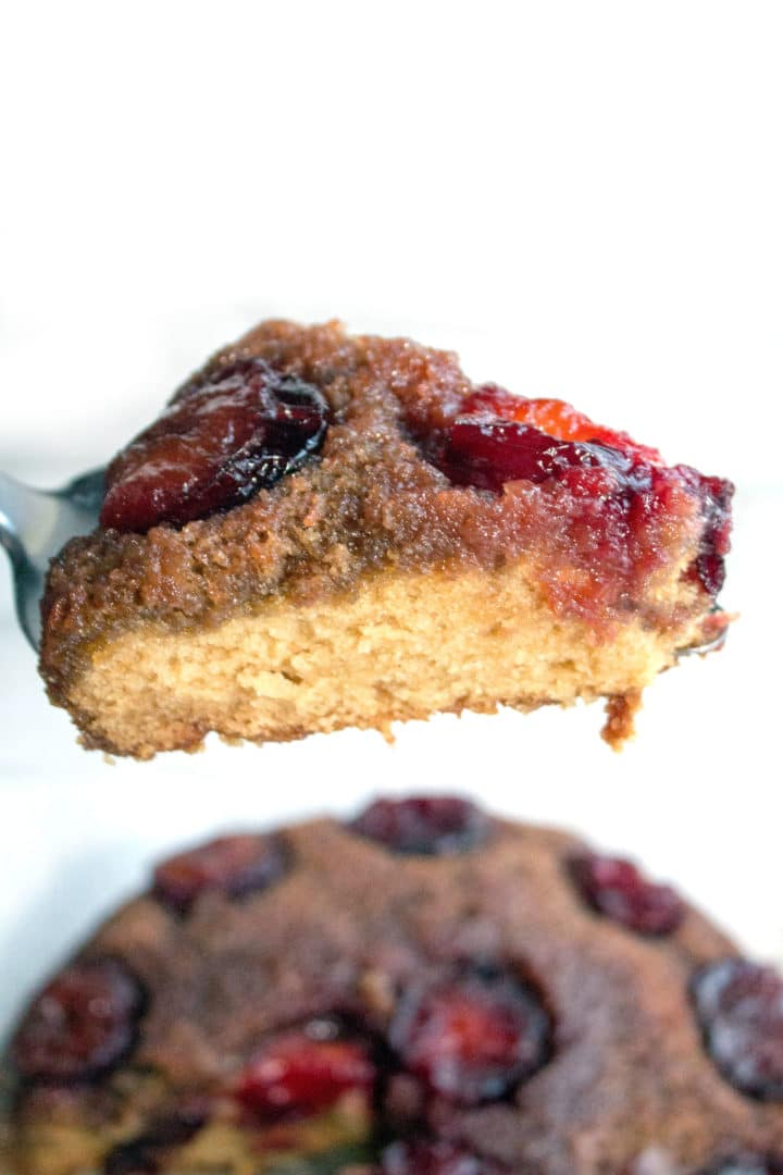 a piece of plum upside down cake on a cake slice, with the rest of the cake in the background