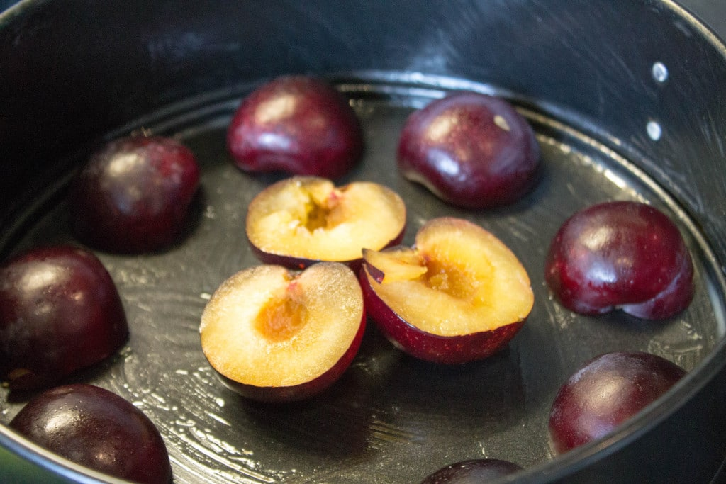 halved plums arranged in a pattern in a pan