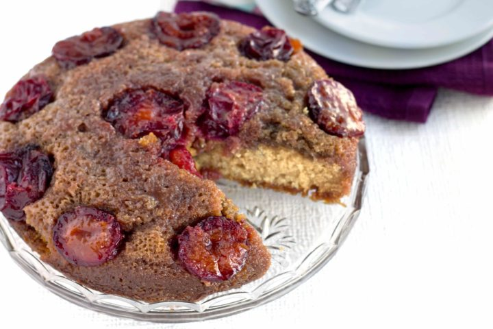plum upside down cake with a slice missing,  on a clear glass plate