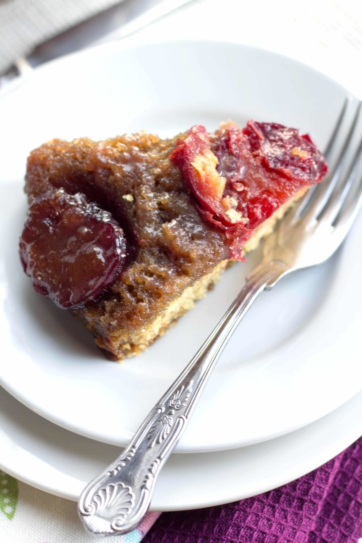 a piece of plum upside down cake on a plate with a fork beside it