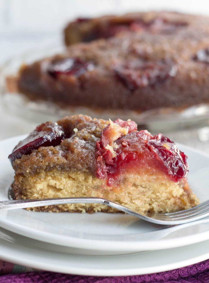 side view of a pice of plum upside down cake on a plate with a fork next to it