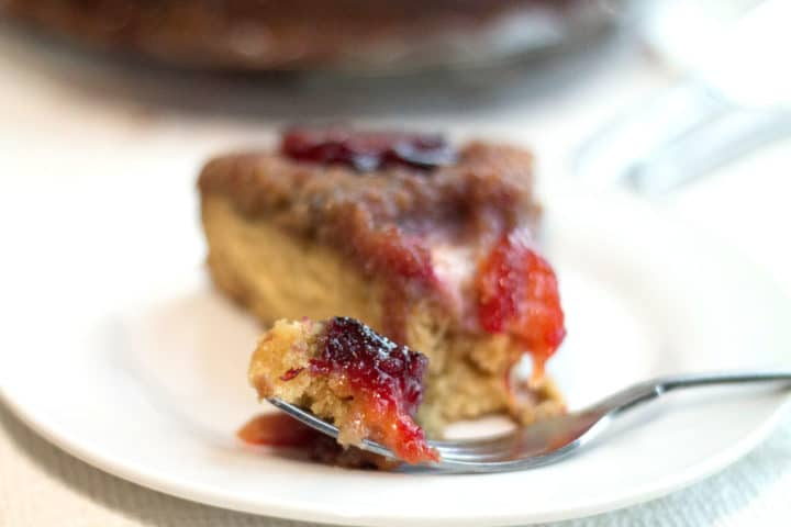 a front view of a piece of plum upside down cake on a plate with a piece of the cake on a fork next to it