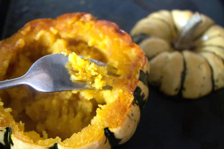 a fork mashing the inside of the squash