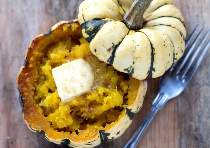 a squash with it's top cut off filled with buttery squash mash with a nob of butter and a fork next to it
