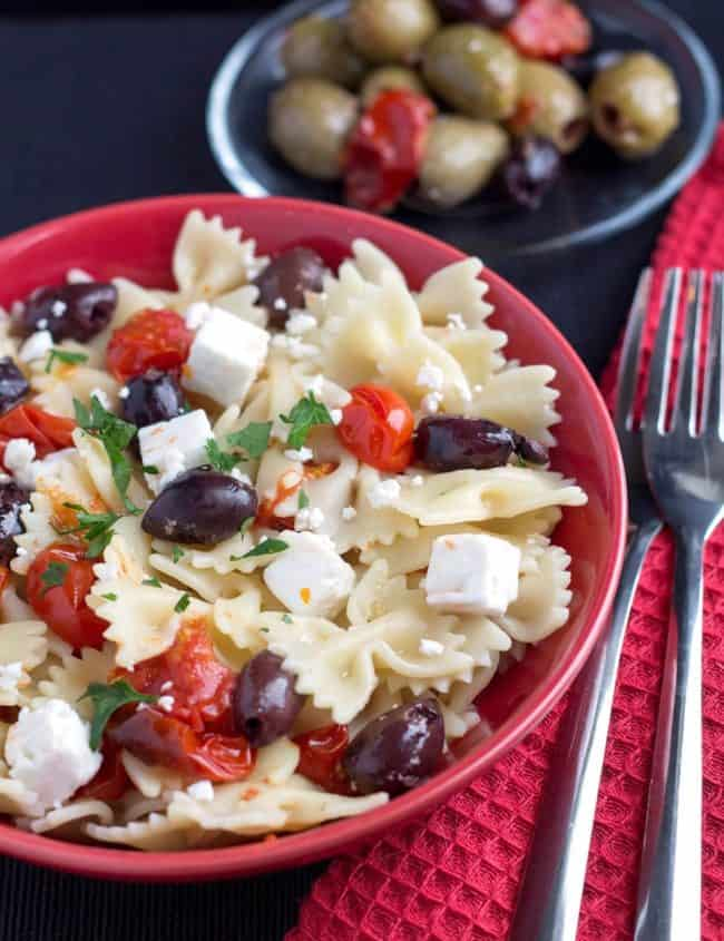 Quick & Easy Pasta with Tomatoes, Feta & Olives in a red bowl with a fork next to it