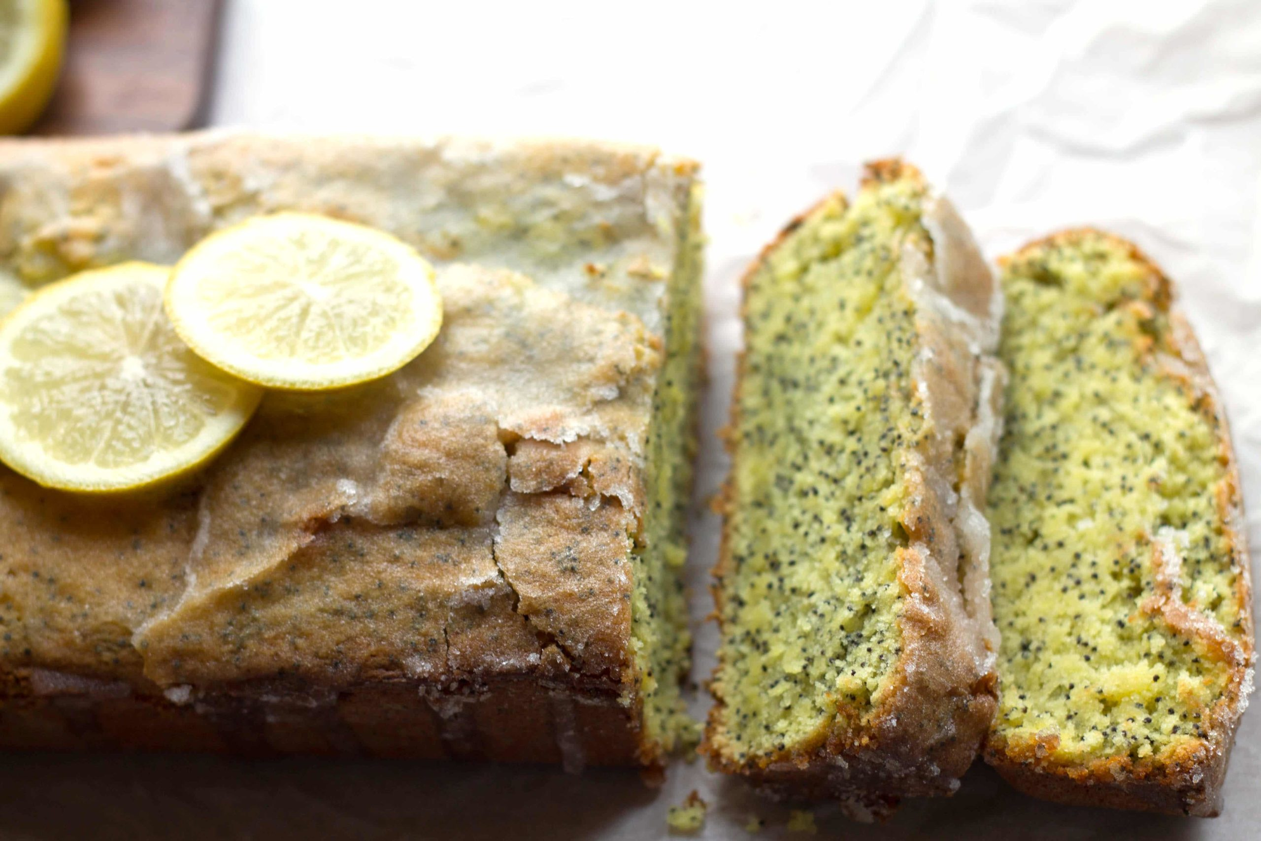 lemon poppy seed drizzle cake with two slices and lemon slices on top