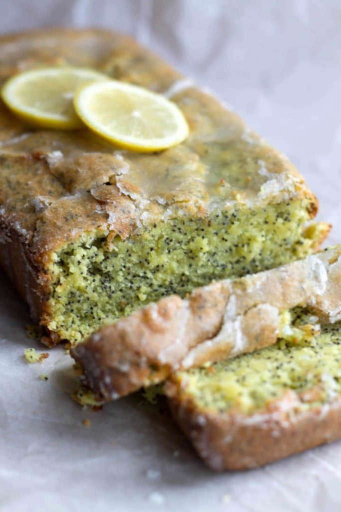 A close up of the Glazed Lemon Poppy Seed Loaf Cake topped with slices of fresh lemon with two slices cut from it