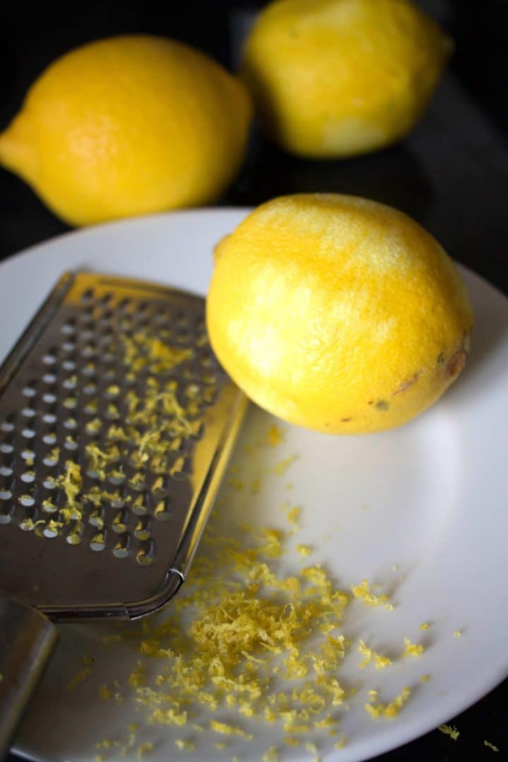 1 Lemon partially zested on a plate with a zester and zest sitting next to it