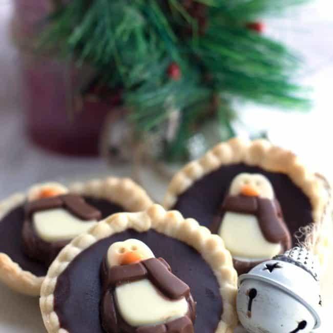 Dark Chocolate Ganache Tarts decorated with penguin chocolates on a plate
