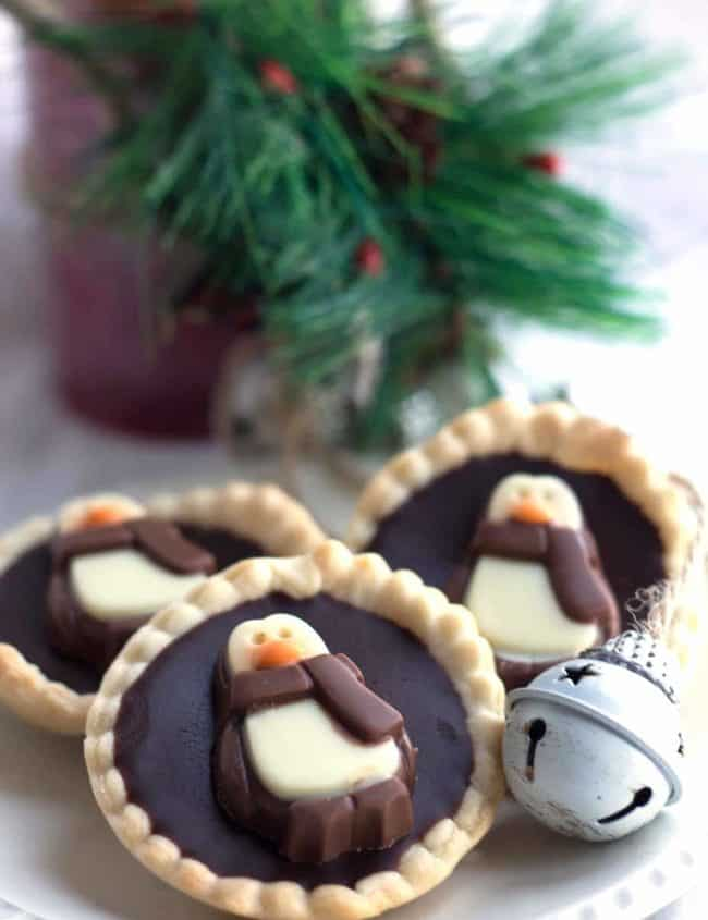 Dark Chocolate Ganache Tarts decorated with penguin chocolates on a plate