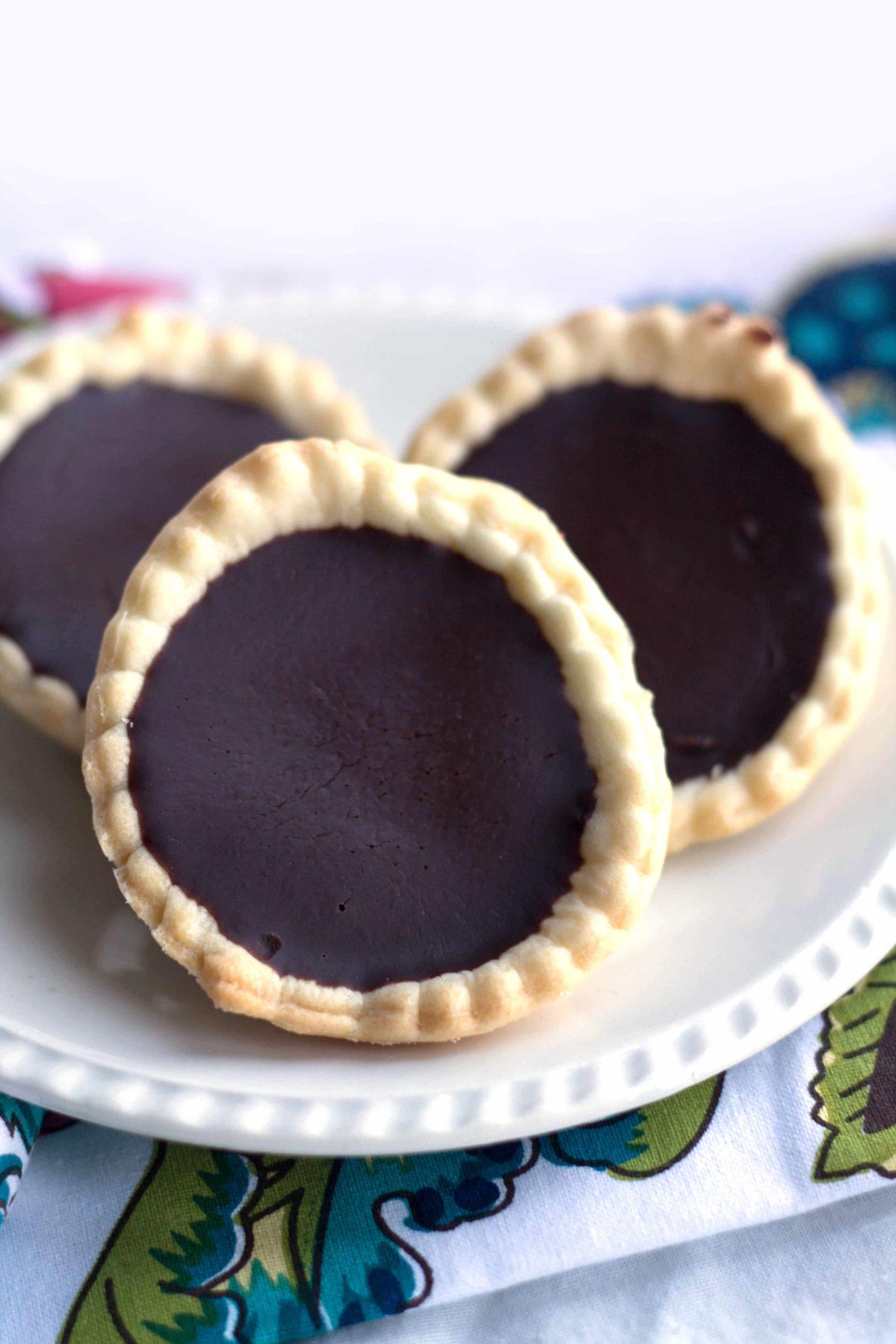 three plain chocolate ganache tarts on a white plate
